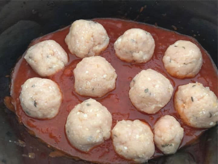 Raw meatballs in pasta sauce ready to cook.