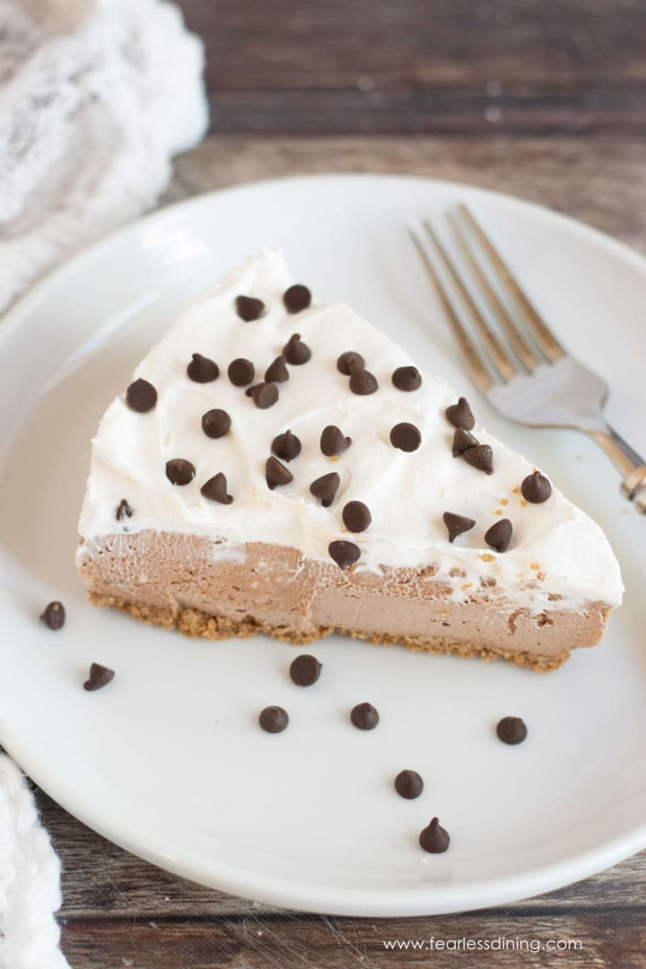 a slice of Nutella cheesecake on a plate. The cheesecake is topped with whipped cream and mini chocolate chips.