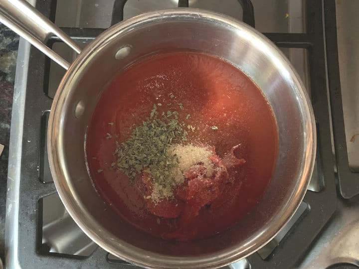 tomato sauce, tomato paste, and spices in a pan on the stove.