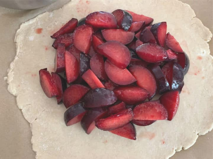 plum mixture on top of a bottom round pie crust. The crust is ready to fold up over the outer edge of the fruit pile.