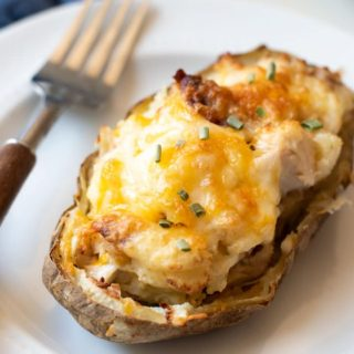 a loaded twice baked potato on a plate with a fork