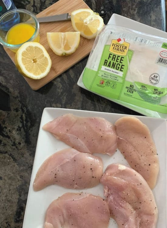 raw chicken breasts on a plate with seasoning