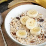 a close up of a bowl of muesli with sliced bananas