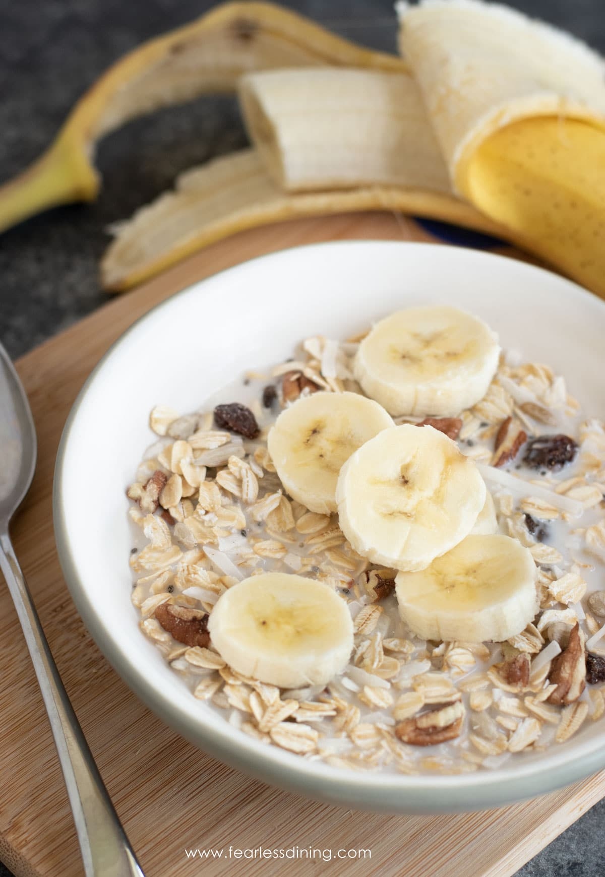 a bowl of muesli topped with sliced bananas