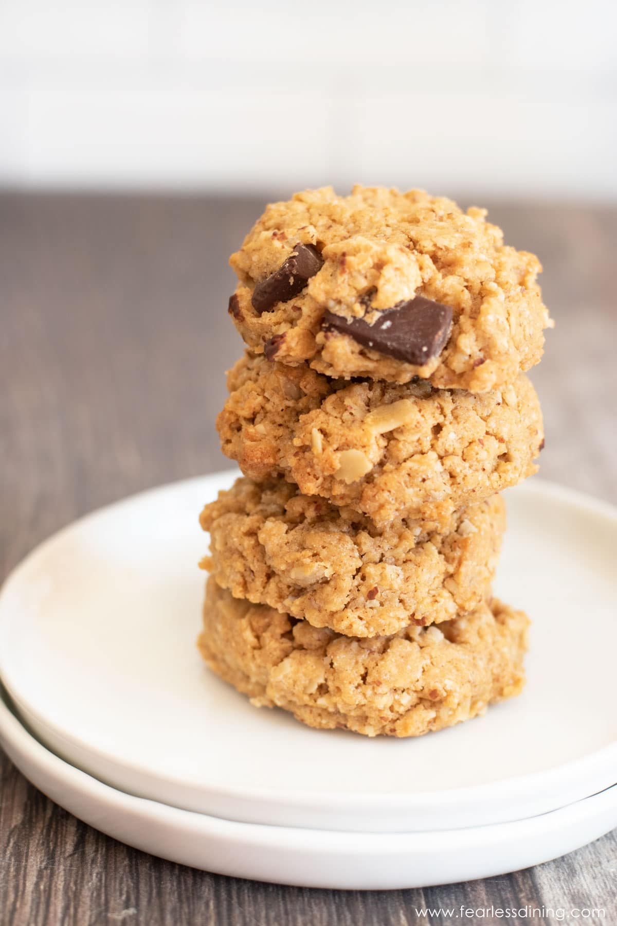 a stack of four gluten free peanut butter oat cookies on a white plate