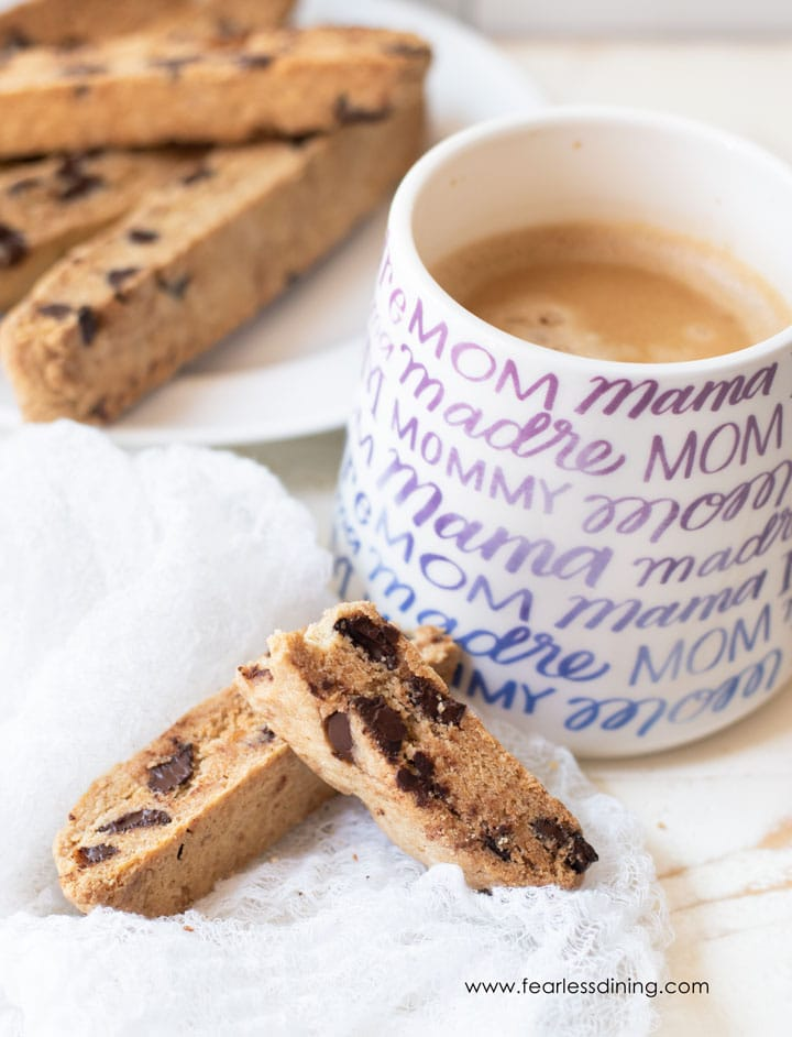 gluten free chocolate chip biscotti next to a coffee mug. A plate of biscotti is also behind the mug.