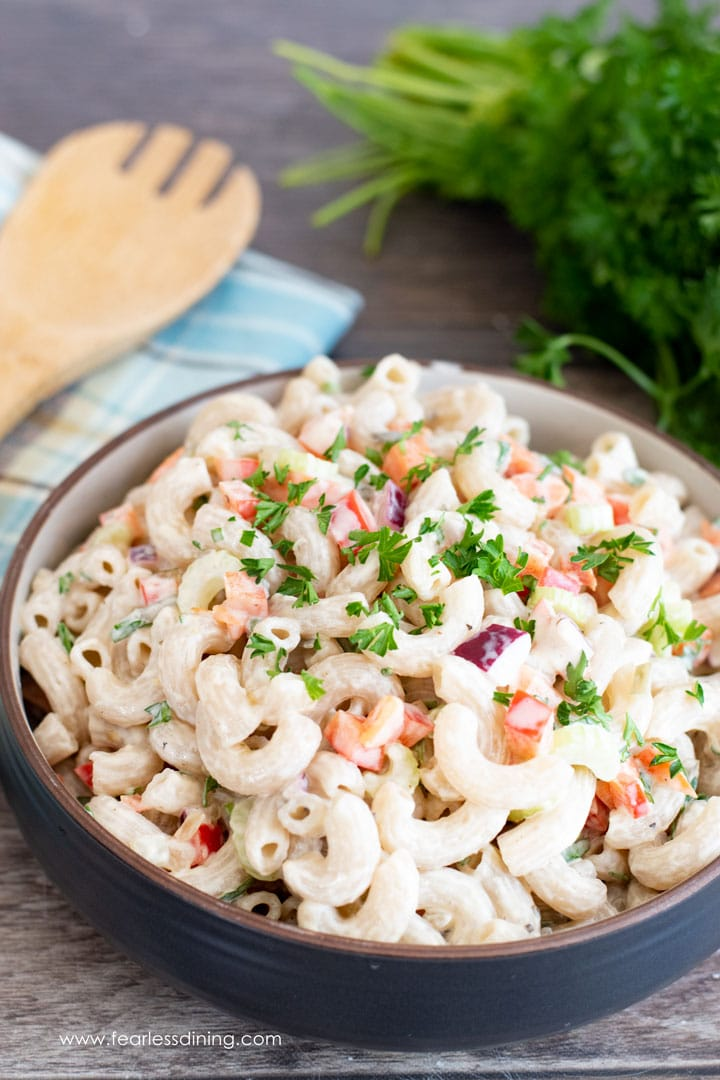 a big bowl of deli style macaroni salad with a serving spoon and parsley