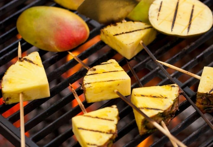 pineapple and mango cooking on a grill