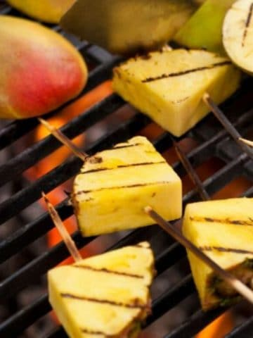 pineapple chunks and mangos on a grill