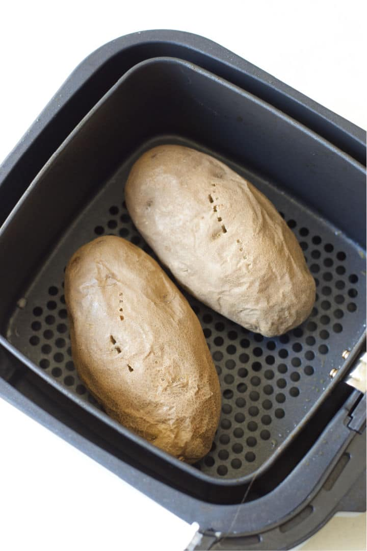 two cooked potatoes in the air fryer