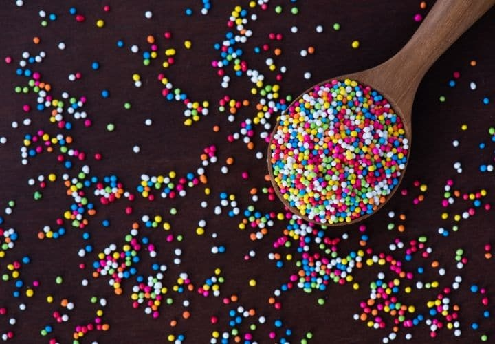 a wooden spoon filled with rainbow colored circle sprinkles
