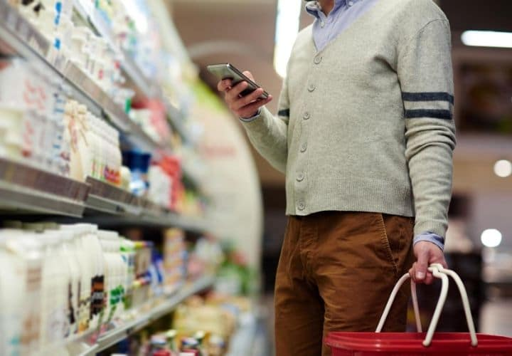 a grocery shopper using phone to check ingredients