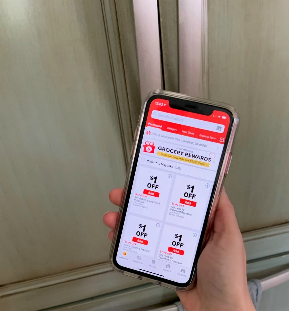 a phone with a grocery store coupon app open
