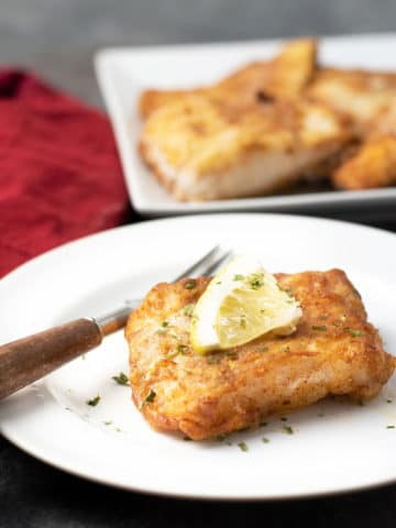 A featured image of a piece of air fried cod on a white plate