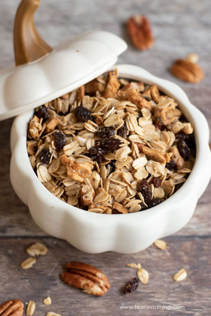 apple granola in a white ceramic pumpkin bowl. The lid is laid slanted next to the bowl