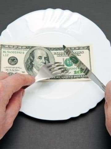 a paper 100 dollar bill on a plate being cut with a fork and knife