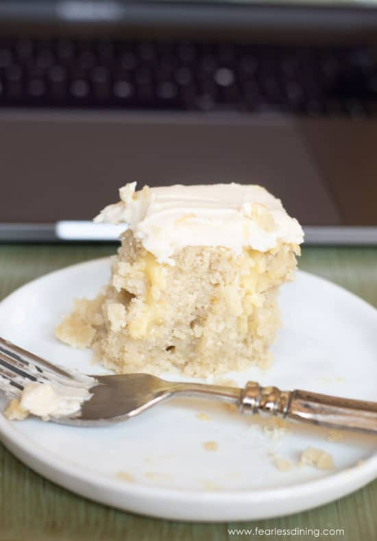 a slice of vanilla poke cake with several bites taken out