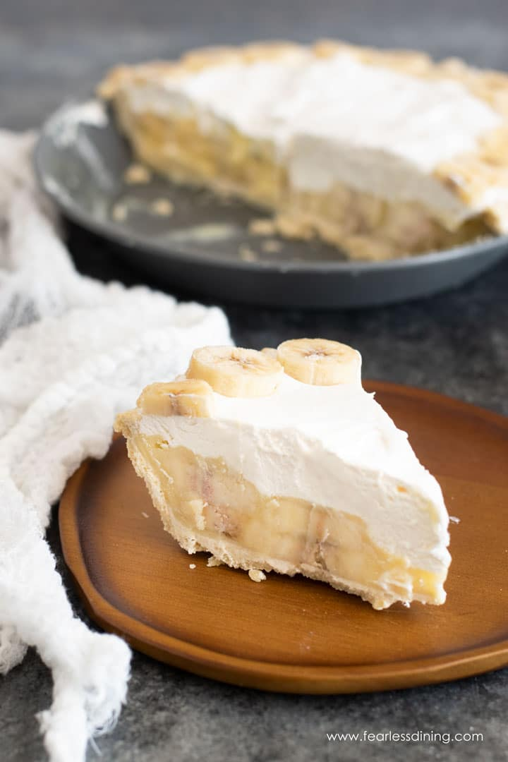 a slice of banana cream pie on a wooden plate