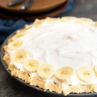 a whole banana cream pie with wooden plates behind the pie
