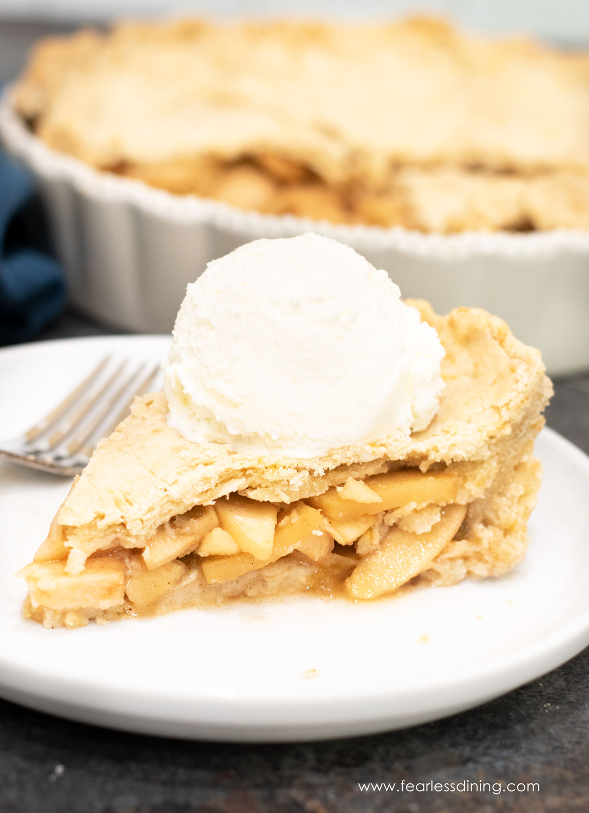 A slice of gluten free hatch chile apple pie on a plate. The slice is topped with a scoop of vanilla ice cream