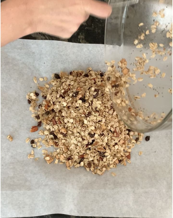 dumping the granola mixture on a cookie sheet