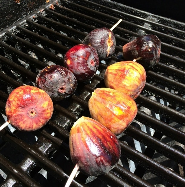 figs on skewers cooking on a grill
