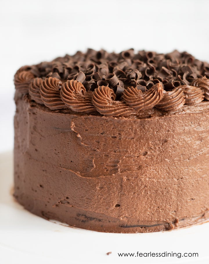 a chocolate frosted cake on a white plate