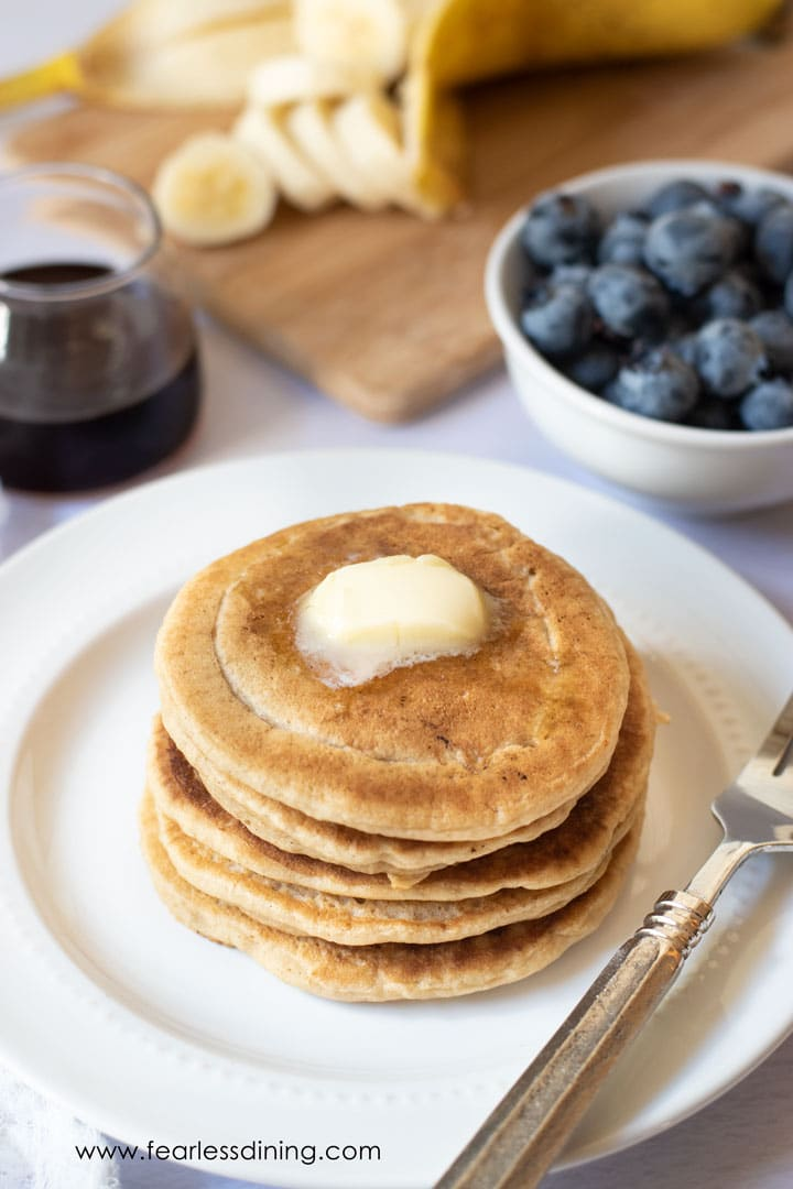 a stack of gluten free pancakes on a plate. There is a wedge of butter on top.