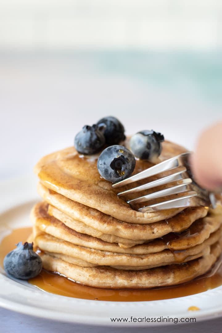 a fork cutting through a stack of pancakes