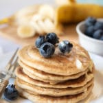 a stack of gluten free pancakes with blueberries and butter on top