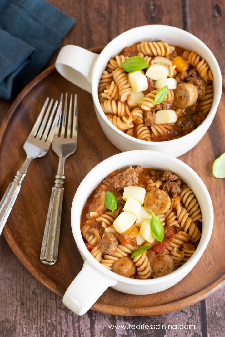 Two bowls of one pot pasta on a wooden tray
