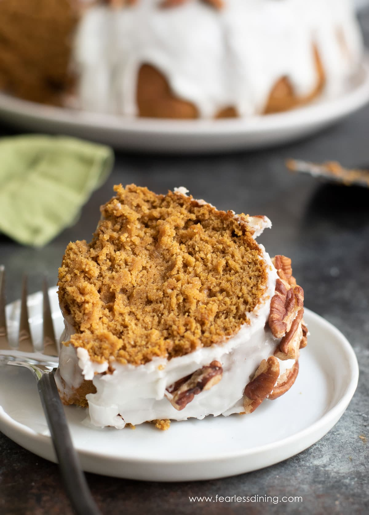 a slice of gluten free pumpkin bundt cake on a plate with a fork