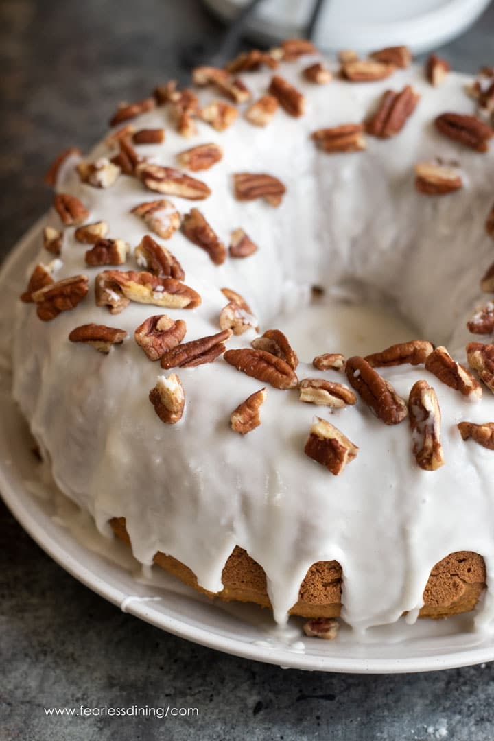 an iced pumpkin bundt cake topped with chopped pecans
