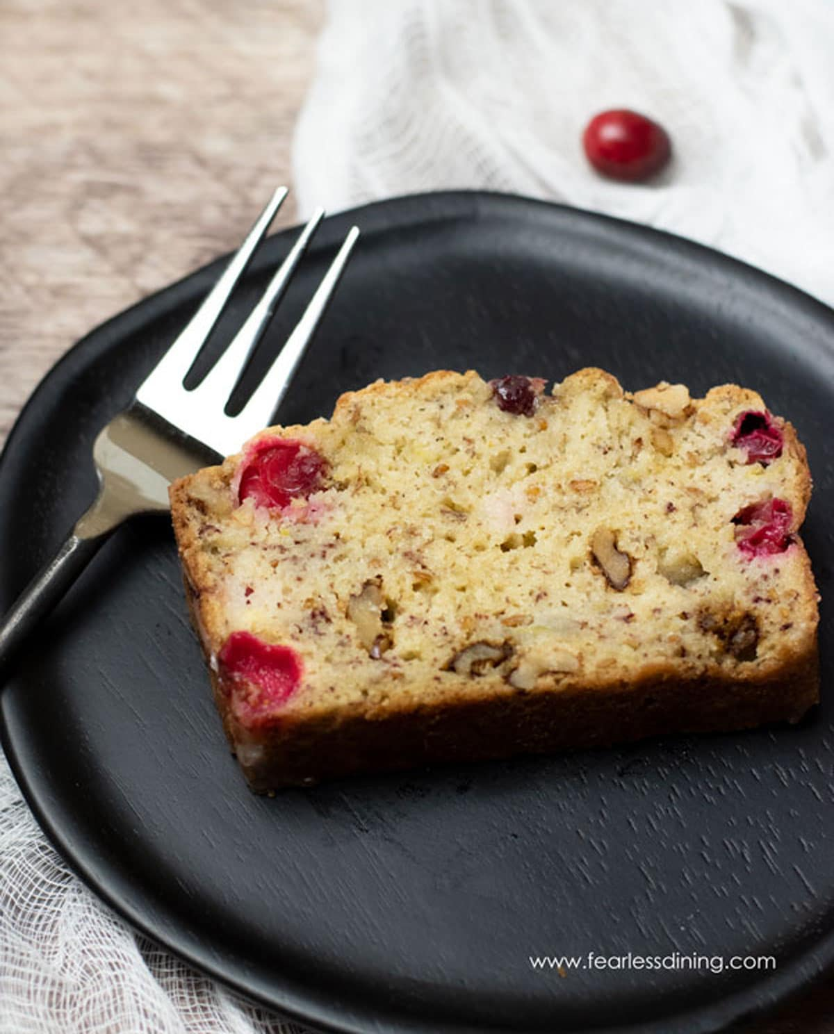 a slice of cranberry banana bread on a wooden plate