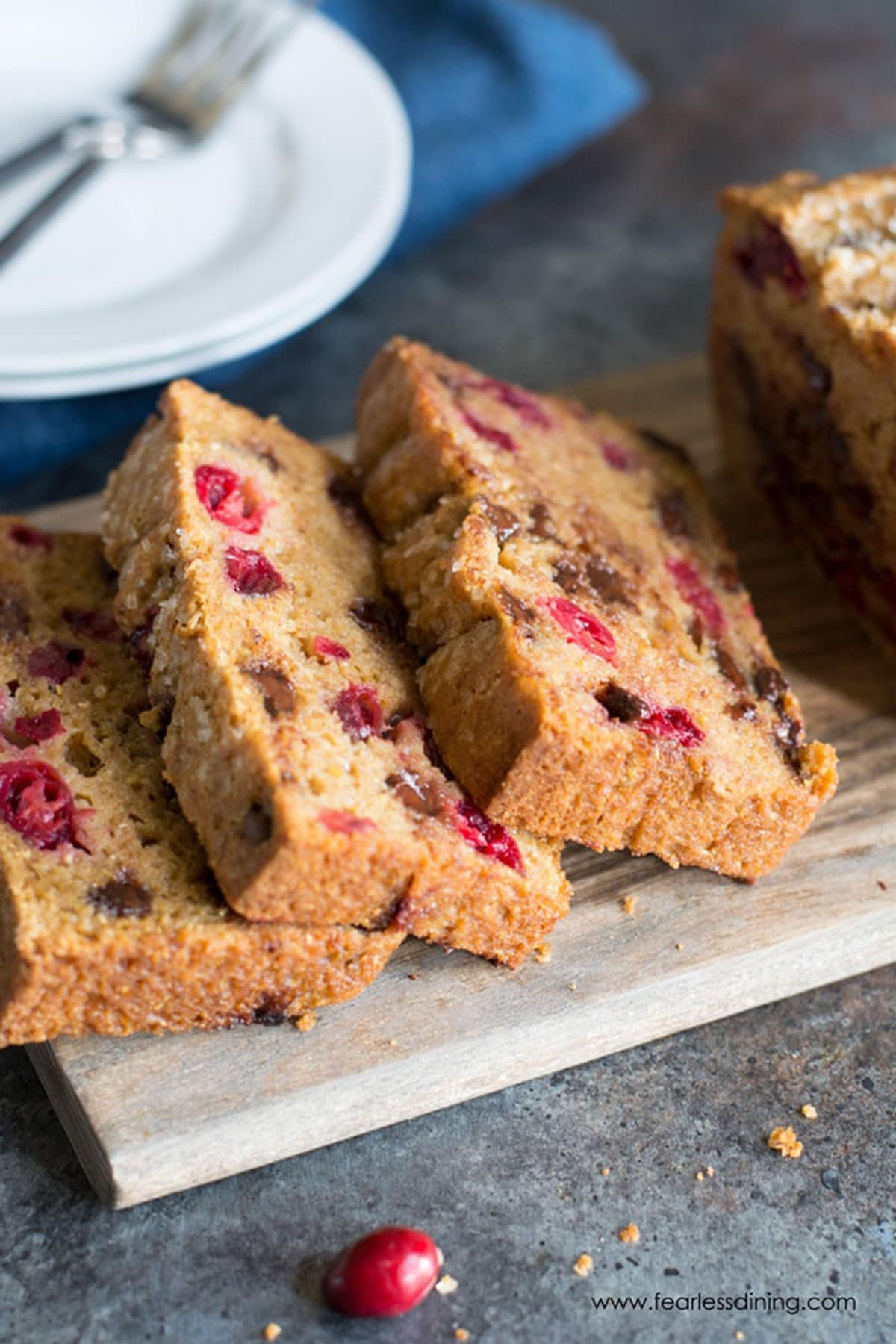 A sliced cranberry chocolate chip loaf on a cutting board