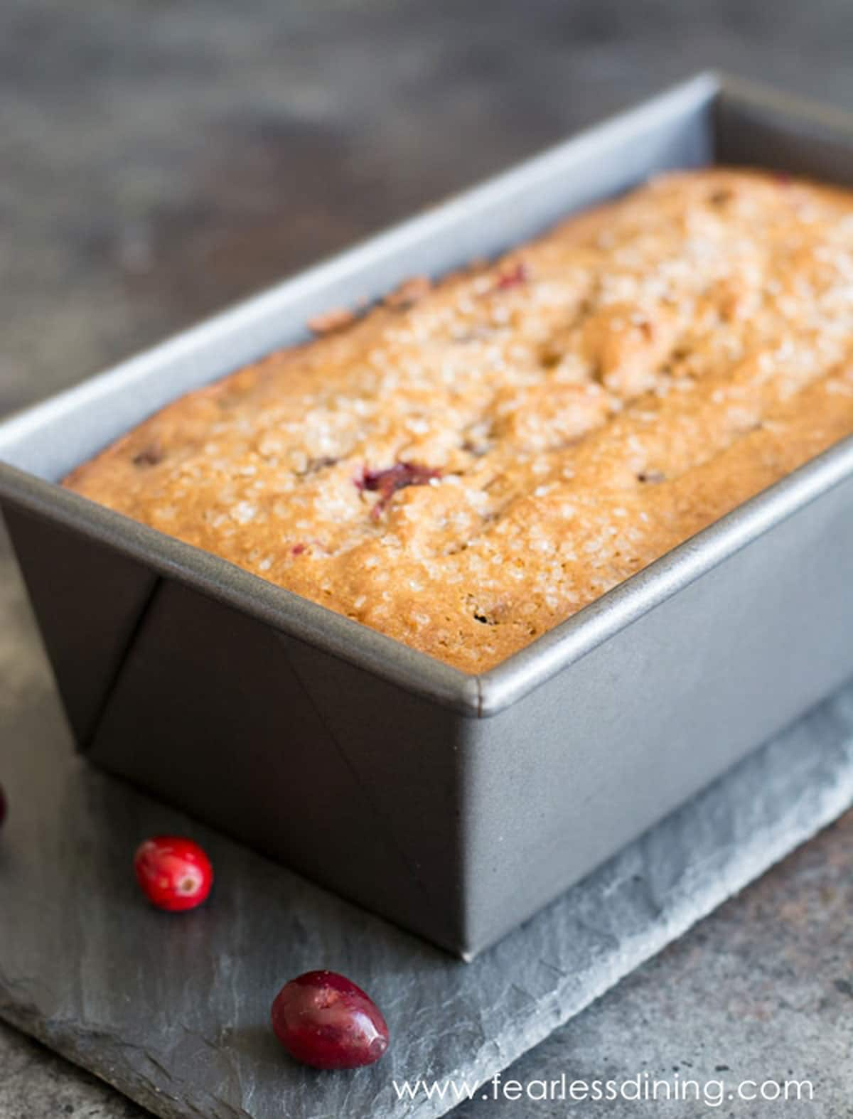 a baked cranberry bread in a loaf tin
