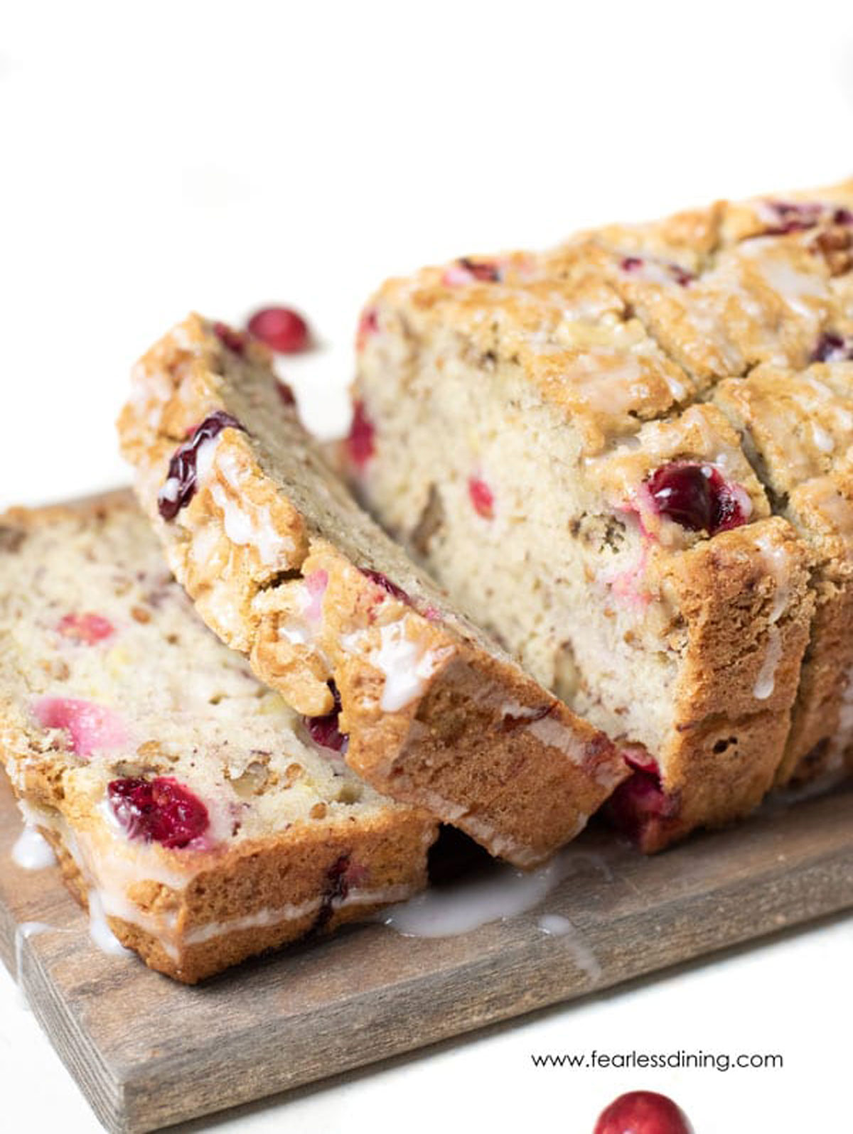 a sliced loaf of banana cranberry bread on a cutting board