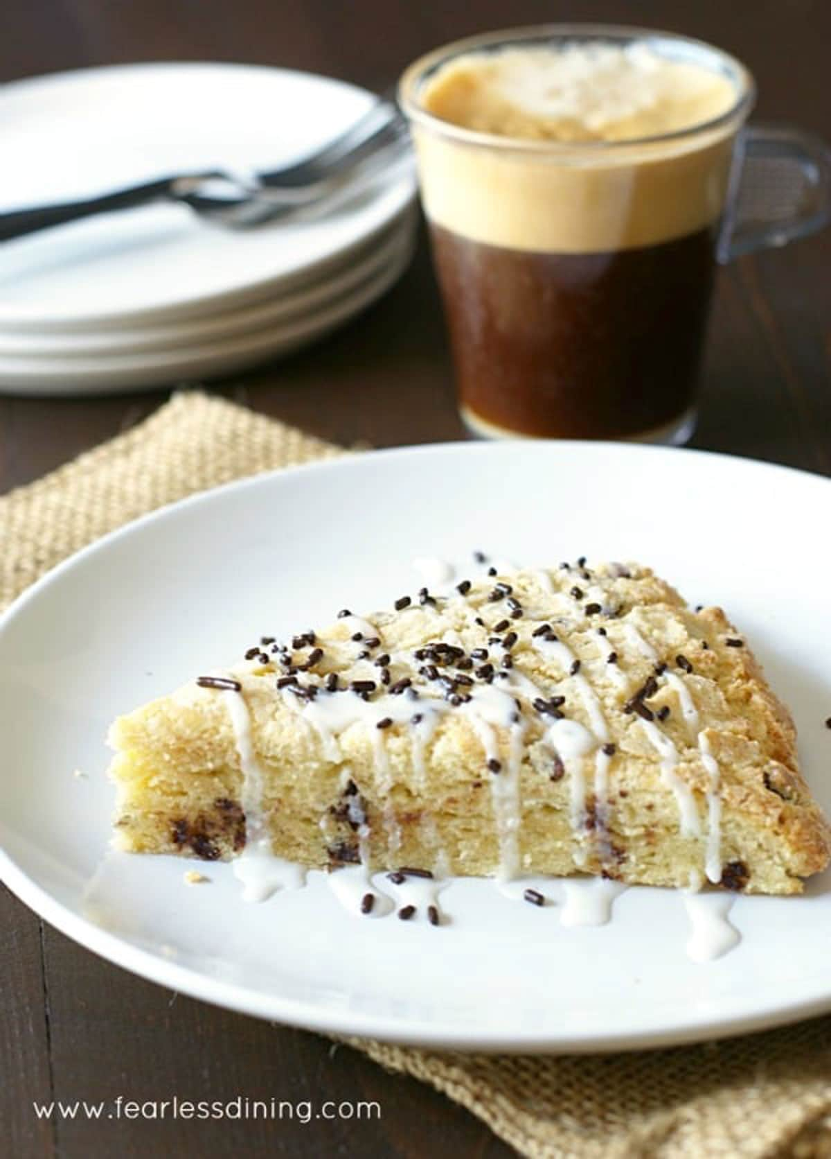 an eggnog scone on a plate next to a mug of coffee