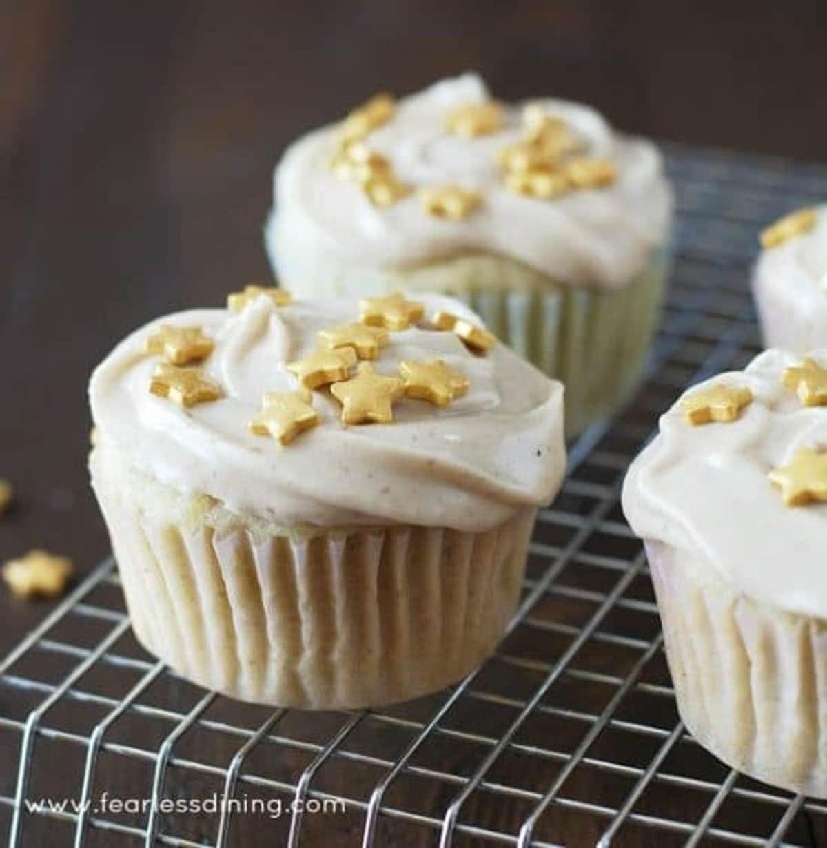 decorated eggnog cupcakes on a rack