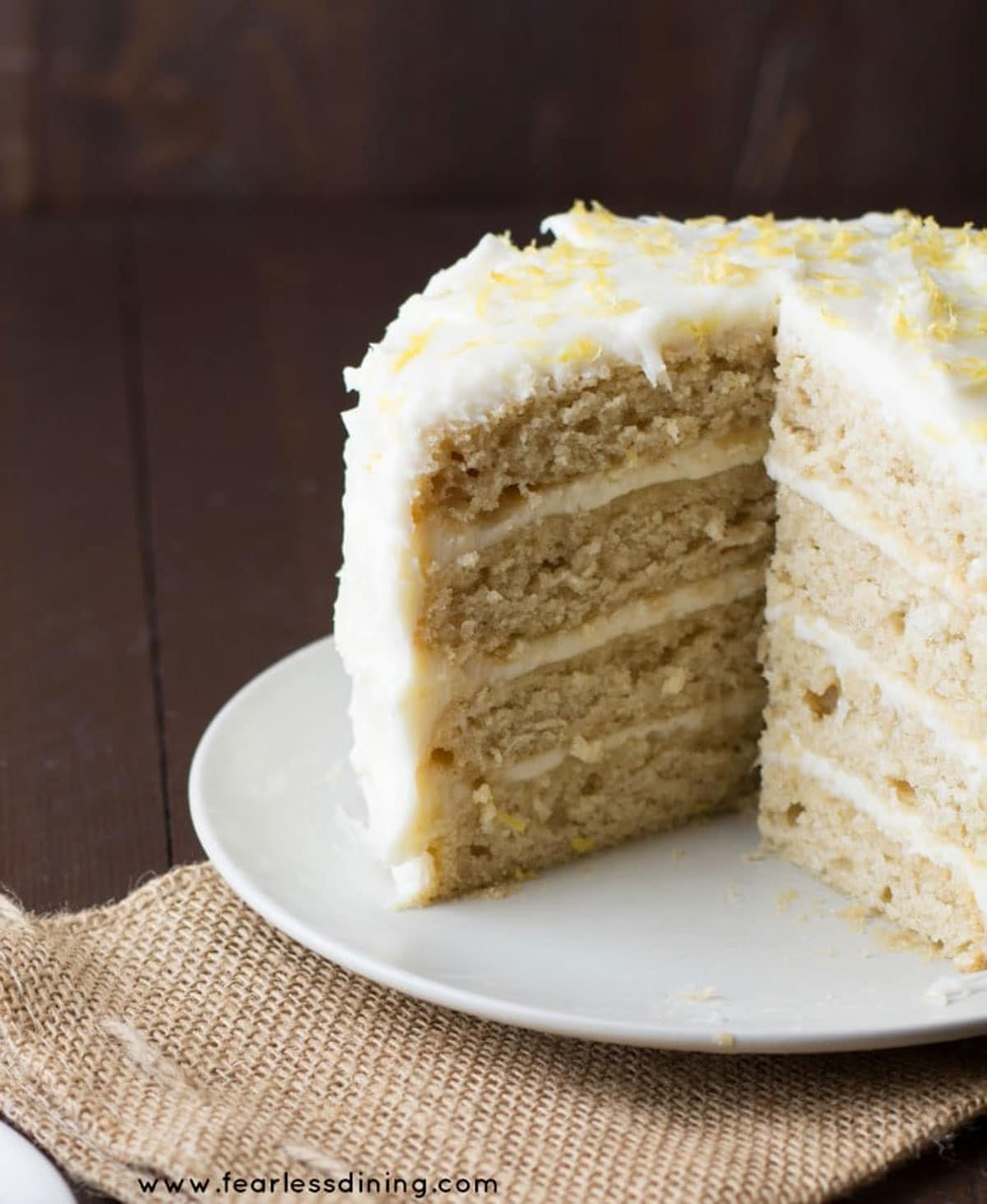 a whole lemon cake with a slice cut out