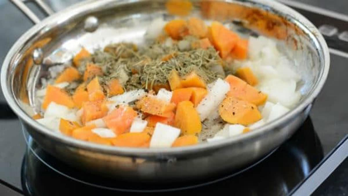 persimmon onion and herbs cooking in a frying pan