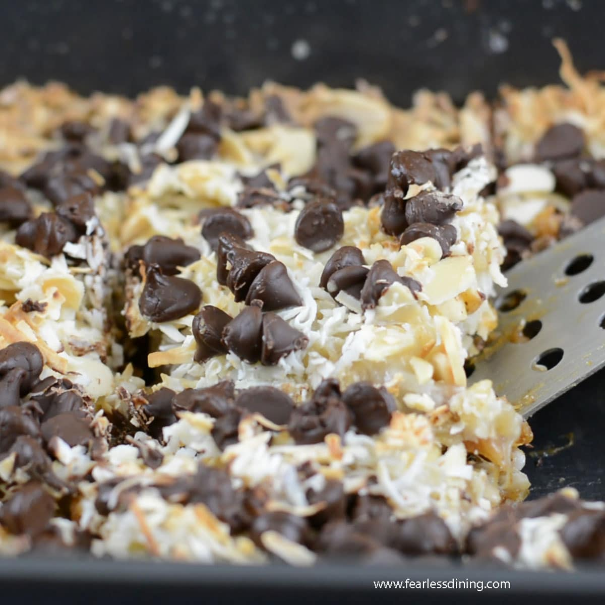 scooping out a slice of gingerbread 7 layer bars