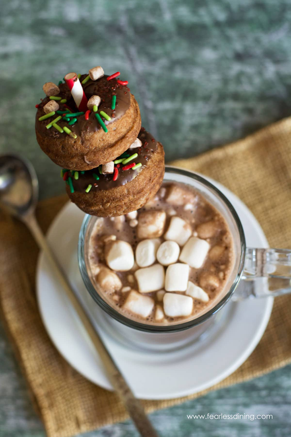 donuts stacked on a straw in a mug of hot cocoa