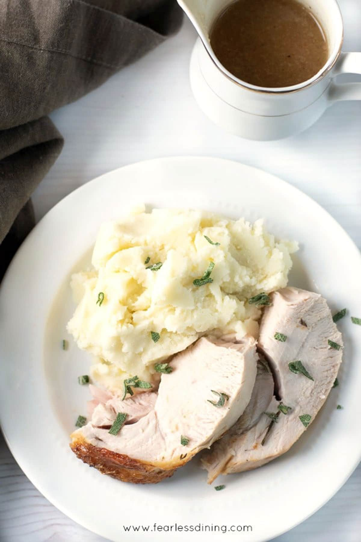 cooked sliced turkey breast next to mashed potatoes on a plate