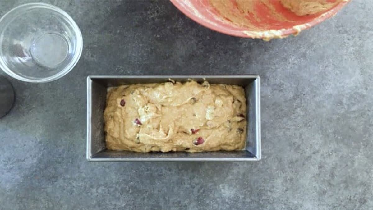 cranberry bread batter in a bread loaf tin