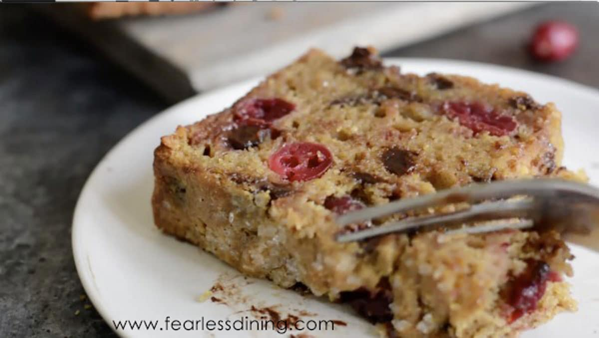 a fork cutting into a slice of cranberry bread
