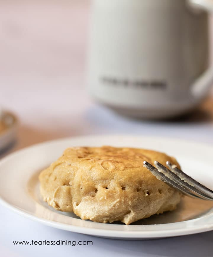 an English muffin on a plate with a fork