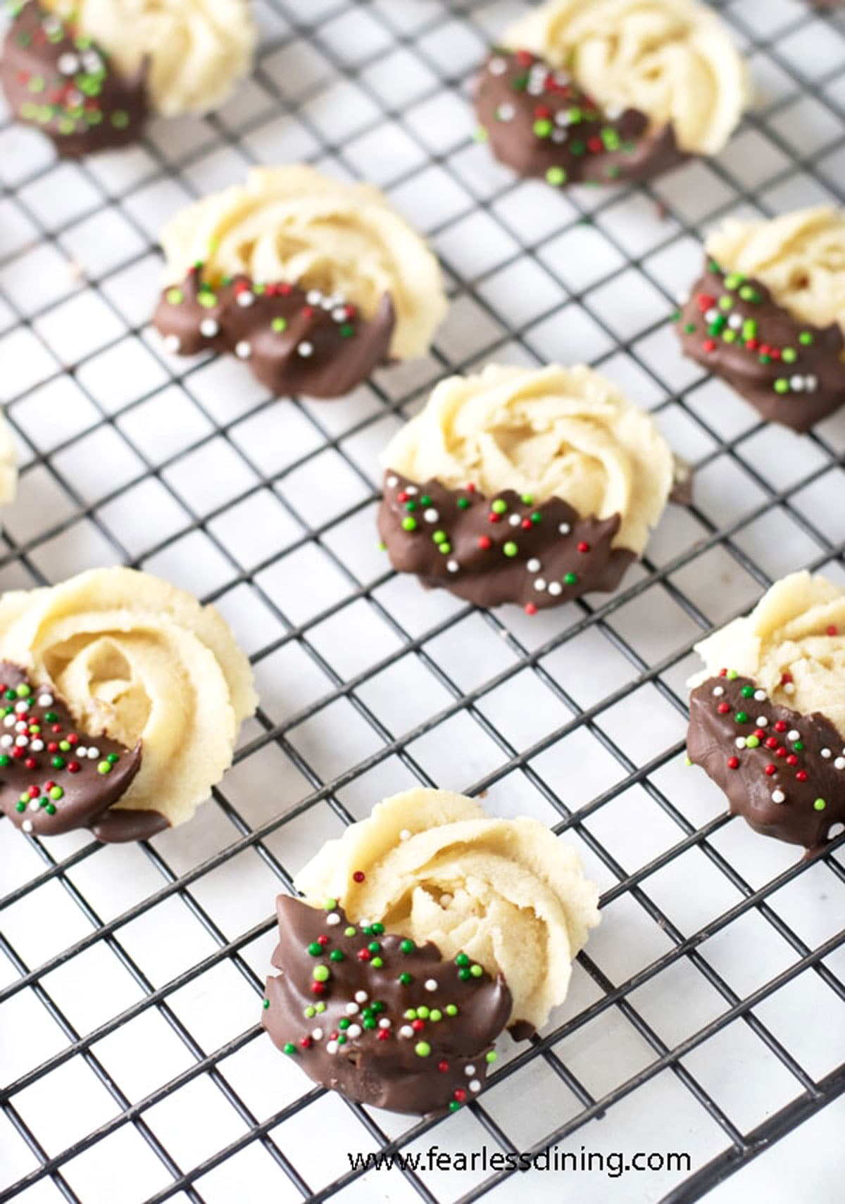 a rack of chocolate dipped butter cookies on a rack