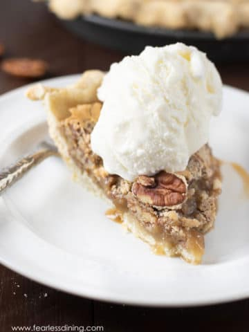 a slice of pecan pie topped with a scoop of vanilla ice cream