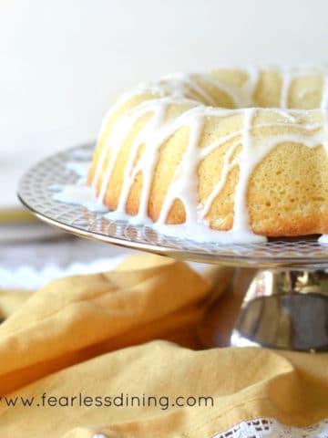 the side view of an iced lemon bundt cake on a platter